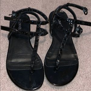 Black sandals with studded texture on straps.
